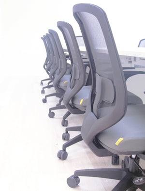 Row of office chairs with black backrests