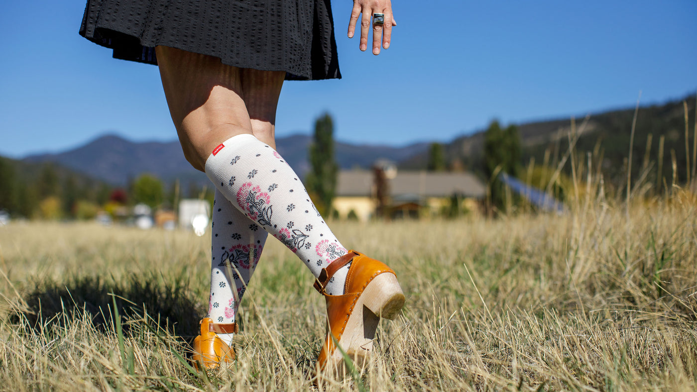 woman wearing compression socks while sitting on a couch