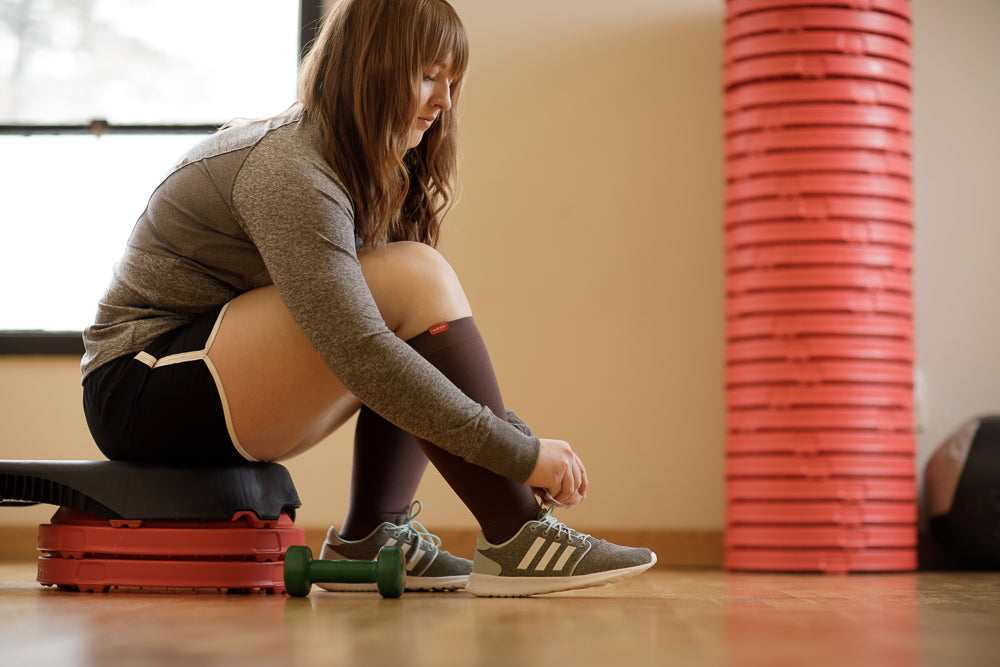 Woman tying her shoes in a gym