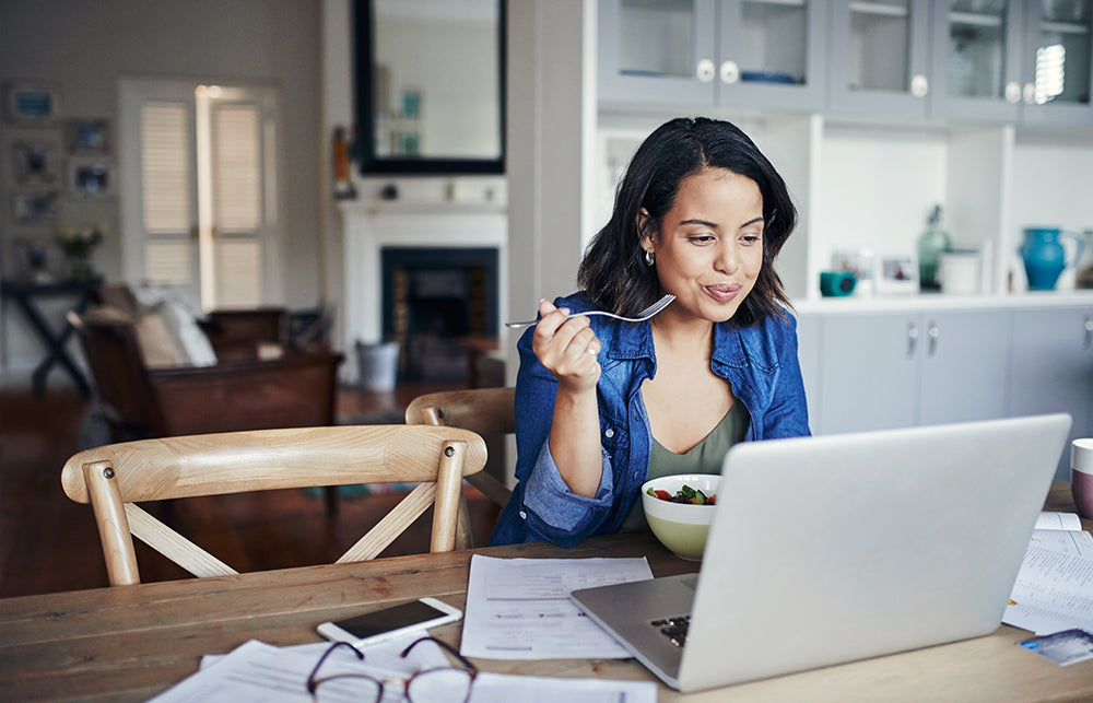 Woman eating salad at her computer