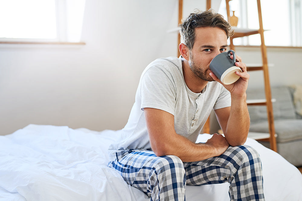 Man sitting on bed in pajamas