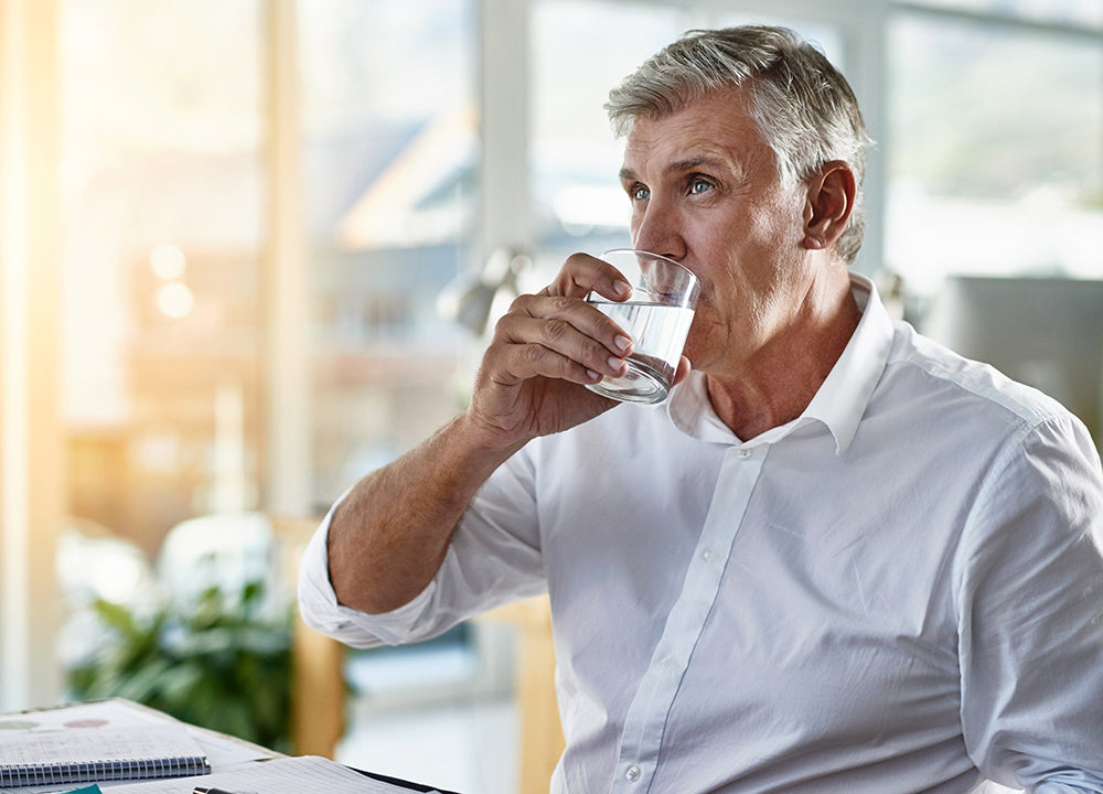 Man drinking water at hes desk