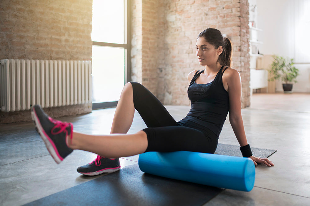 Woman rolling her legs with foam roller