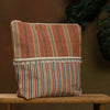 Striped terracotta coloured pouch. With tassle trim and contrast stripes.