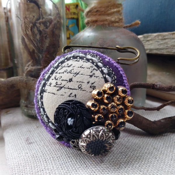 Padded fob brooch with gothic script and vintage buttons.