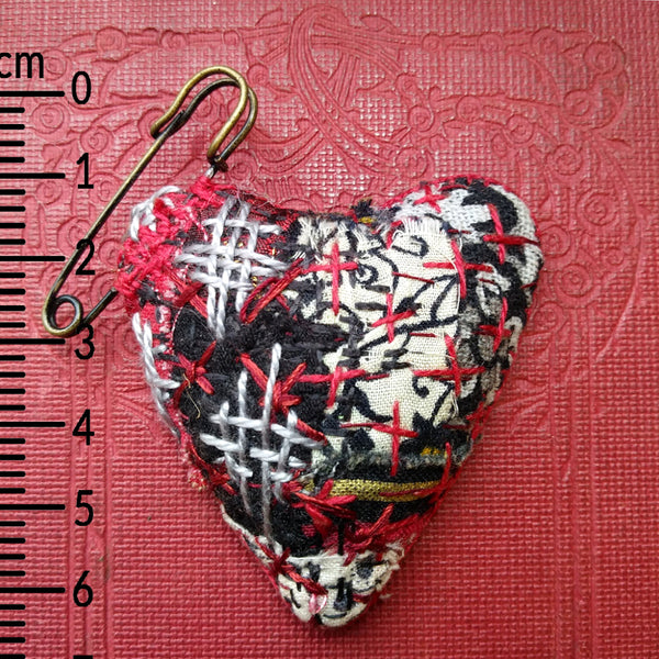 Padded patchwork heart shaped brooch on kilt pin Hand stitched in Boro style. Red and Black.  Showing ruler for scale