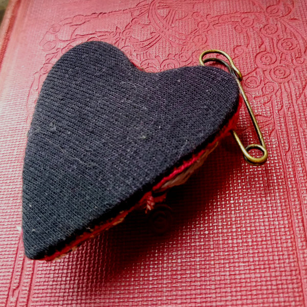 Padded patchwork heart shaped brooch on kilt pin Hand stitched in Boro style. Red and Black.  Back view showing black back of brooch.