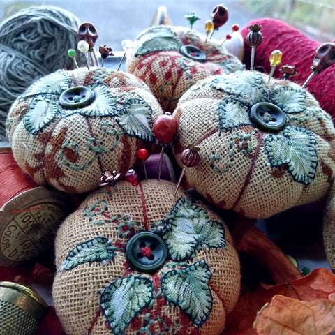 Pumpkin pincushions with spools and autumn leaves