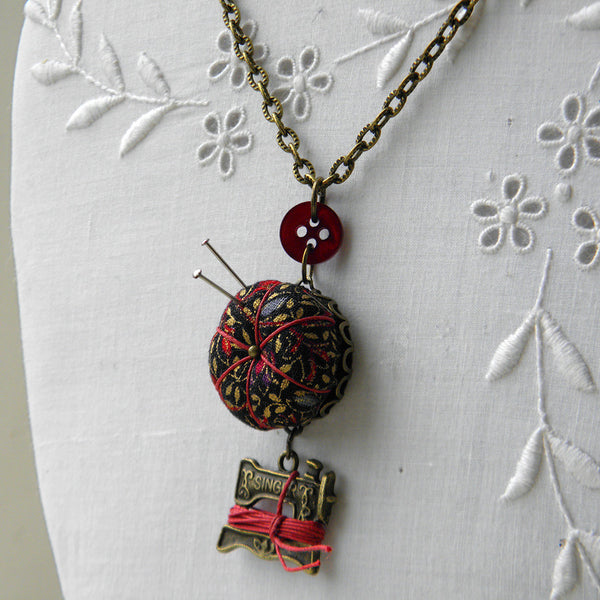 Miniature pincushion necklace with sewing machine thread winder charm.