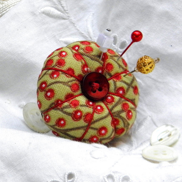 Pincushion ring in festive red berries design with a red button.