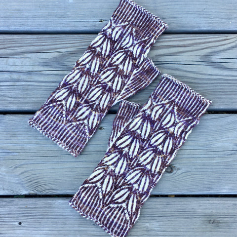 a pair of fingerless mitts knit in brown yarn with a contrasting white yarn pattern.