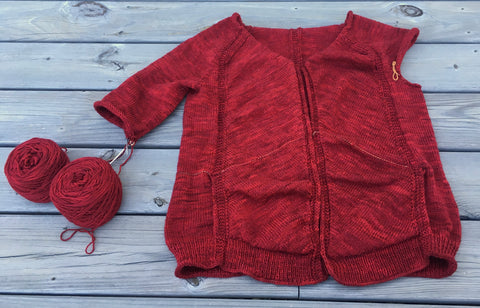 a handknit red sweater, with one partially knit sleeve and one sleeve that's yet to be knit