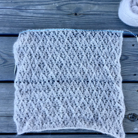 a large rectangle of handknitting in a light colored neutral mohair yarn