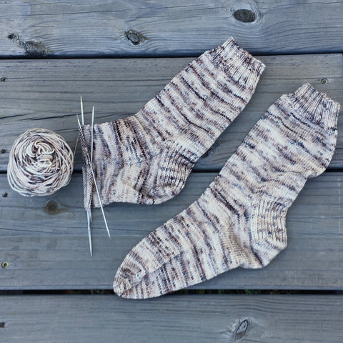 a pair of handknit socks, one partially knit with the needles still attached.