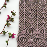 a swatch of brioche knitting placed next to several floral branches