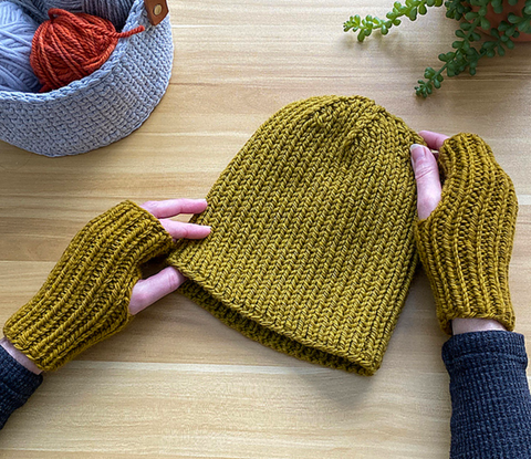 an off-screen person wearing fingerless mitts is holding a hat made from the same yarn in the same color.