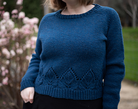 a woman is standing with one hand near her pant pocket. She is wearing a tealish blue cropped sweater