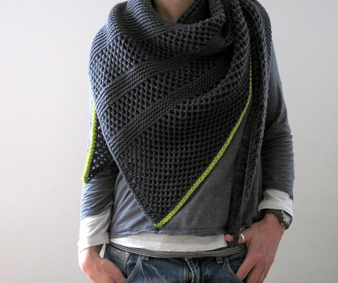 a woman is wearing a charcoal gray shawl around her neck and shoulders.