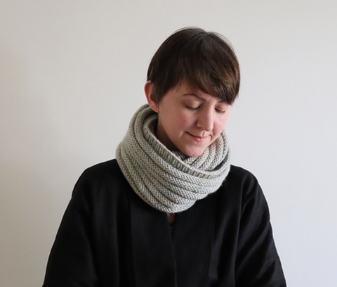 a woman with short brown hair is wearing a light gray cowl, doubled around her neck.