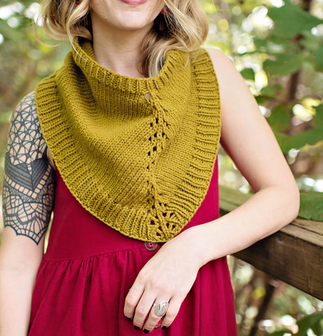 a woman is wearing a mustard colored handknit bandana shaped cowl