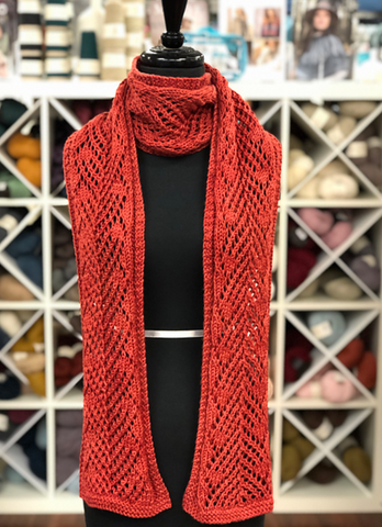 a black mannequin is wearing a scarlet red lace scarf, wrapped once around its neck.