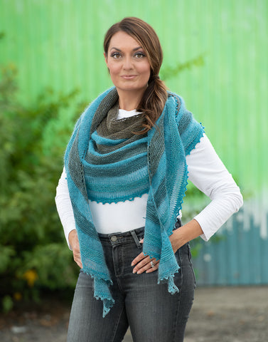 A woman is standing with her hands on her hips, wearing a handknit shawl in varying shades of blue/green.