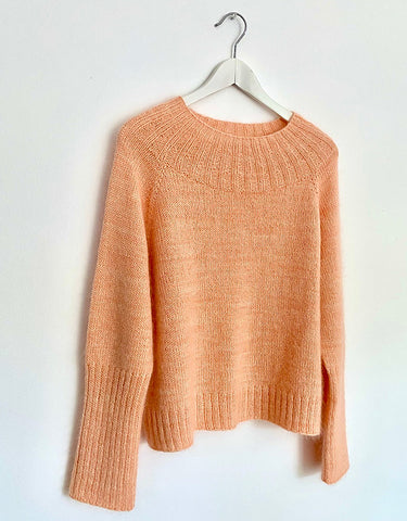 a peach colored sweater with a textured yoke is hanging in front of a white backdrop