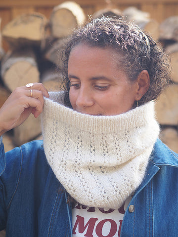 a woman wearing a white handknit fuzzy lace cowl