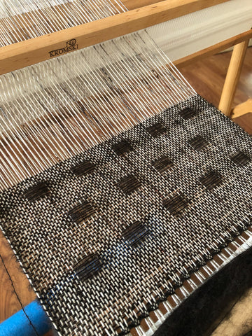 Partially completed weaving on a rigid heddle loom with cream and brown yarns