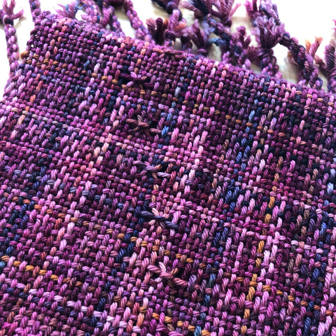 A woven scarf made with variegated purple yarn