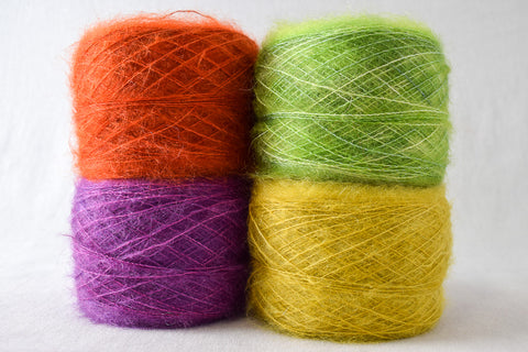 Four cylindrical yarn cakes of mohair-silk blend yarn, in red, purple, green, and yellow