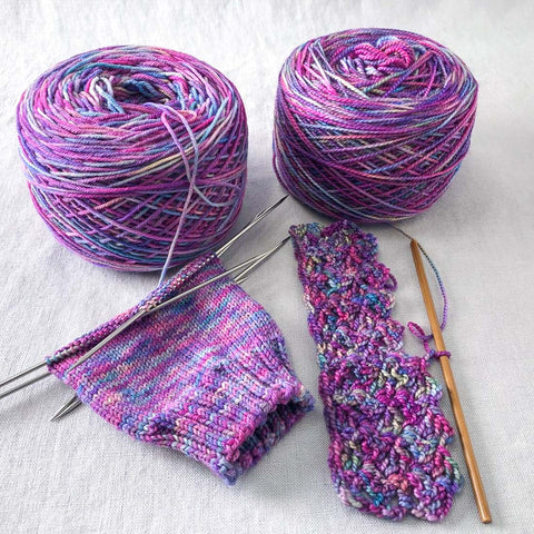 Two 'cakes' of yarn, in a purple-pink colorway. One is partially knit into a sock, the other is partially crocheted.