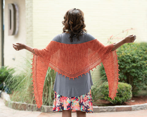 A woman, facing away from the camera, wears a fringed, orange, triangular knitted shawl.