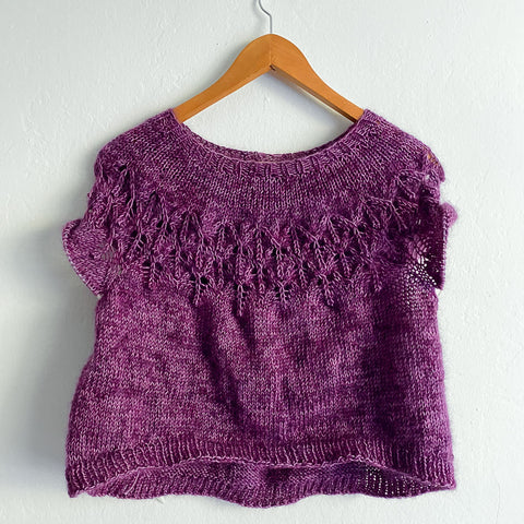 A fuzzy purple sweater in progress hangs on the wall. The body is done but it's missing the sleeves.