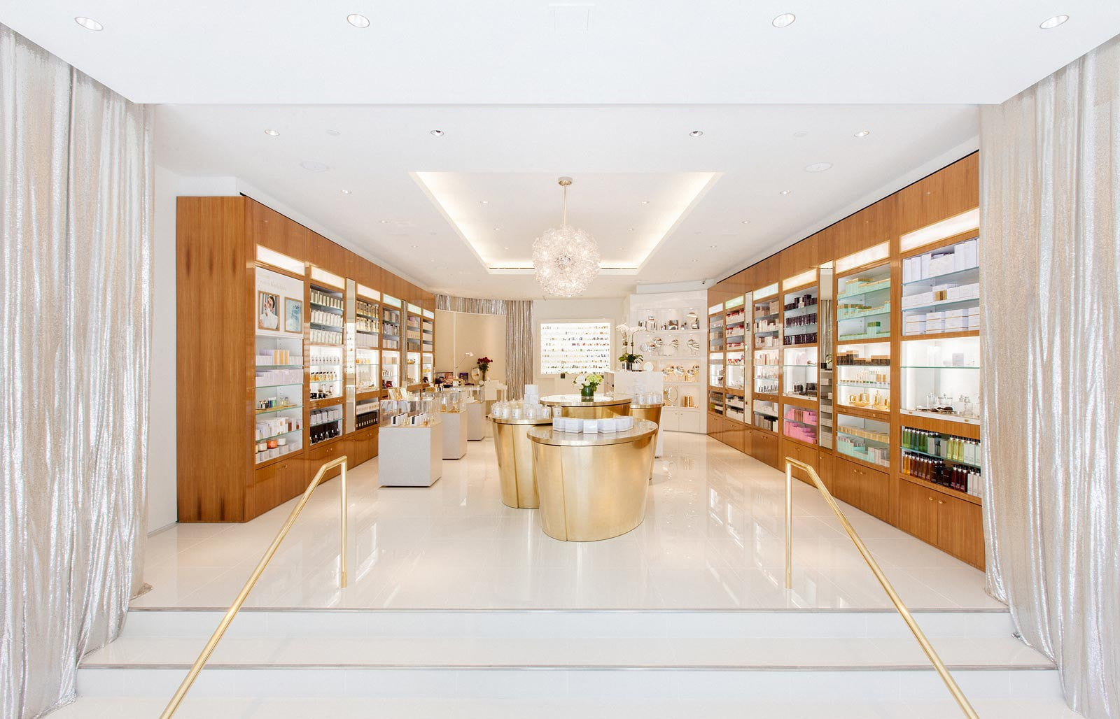 Osswald perfumery in-store image. White floor with large gold metallic display table with perfumes and skincare on it. Walls of cherry red wood with shelves filled with perfumes, skincare, body and beauty products. Back wall a light up case filled with vintage perfume bottles.