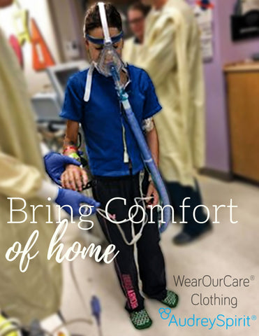 AudreySpirit WearOurCare Child in blue Adrianne Style shirt with many medical tubes and lines and a large mask on their face walking in a hospital hallway surrounded by health care workers
