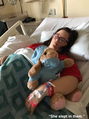 Ellie asleep in Children's Mercy hospital after heart surgery wearing a red AudreySpirit shirt and hugging a teddy bear