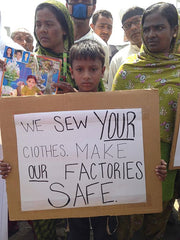 Bangladeshi child holding protesting sign for garment workers' rights