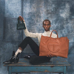 Model holding large and small Telfar shopping bags