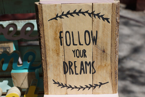 Sign that reads follow your dreams