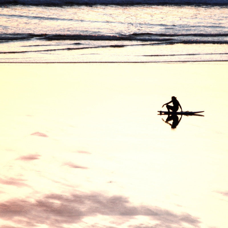 <p>A lone surfer, sits on the beach as the sun sets over the Atlantic at Mawganporth in Cornwall, his reflection in perfect symmetry.</p>