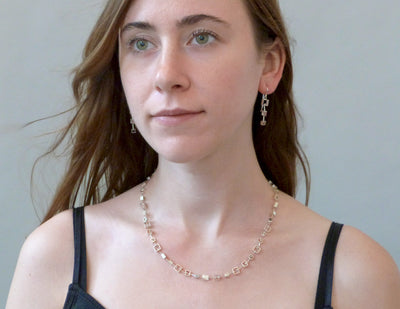 Modern necklace and earrings on model