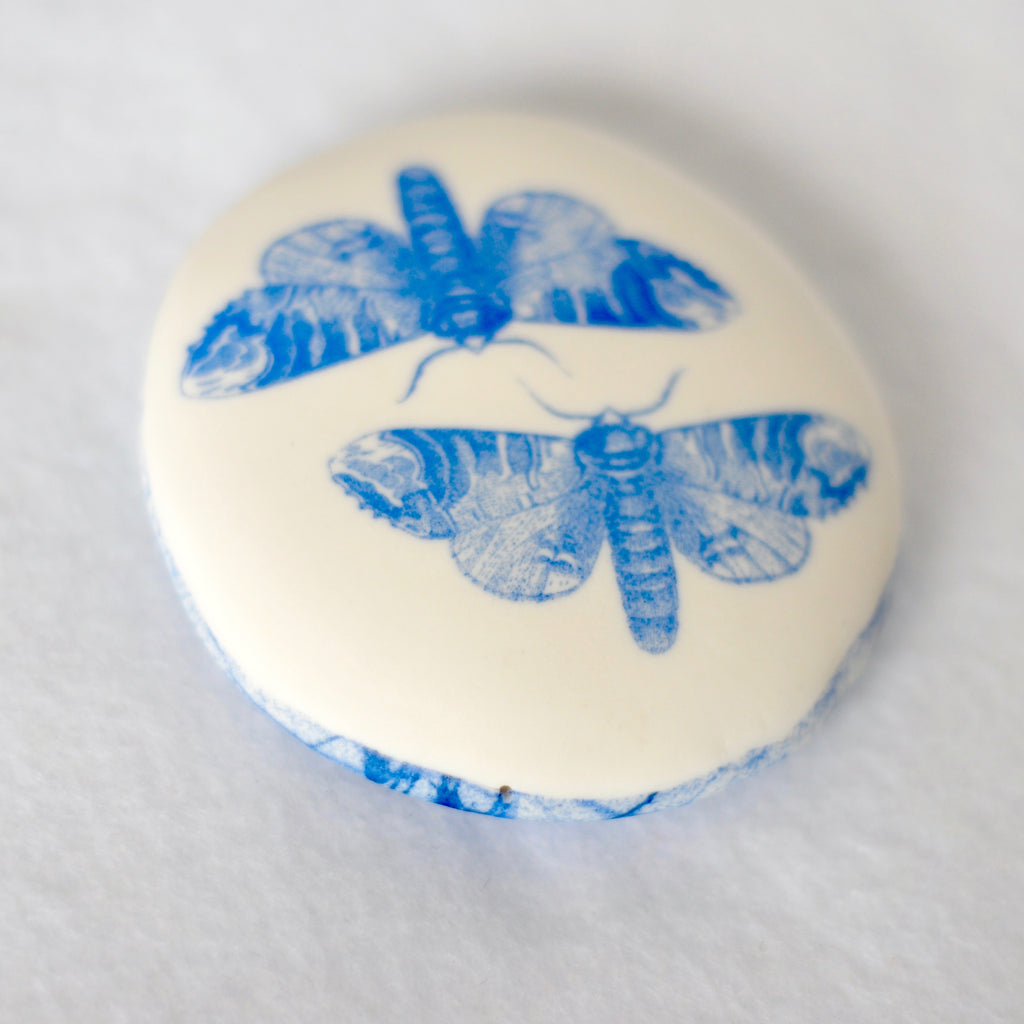 Porcelain pebble with  screen printed images of flowers and butterflies.