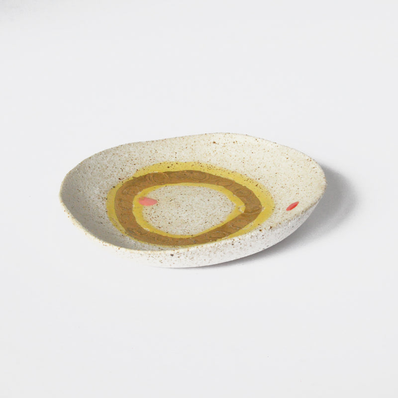 Small decorative plate by Dayle Green with a gold circle and red dots.