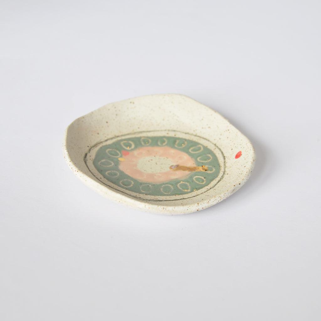 Small decorative plate by Dayle Green with a green and pink circle and red dots.