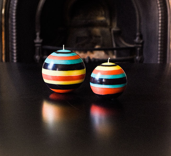 Large striped ball candle in Honey Bird Blue, Jet Black, Jasmine and Rust.