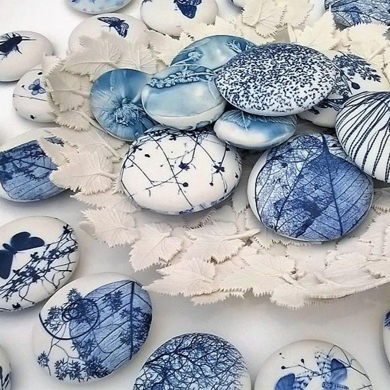 Porcelain pebble with screen printed images of layered leaves