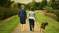 man and woman walking dog in gardens