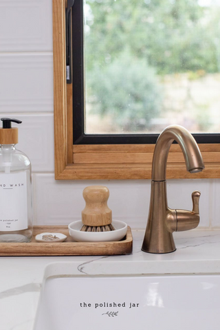 Modern farmhouse kitchen sink counter with wood tray and glass soap dispenser by The Polished Jar