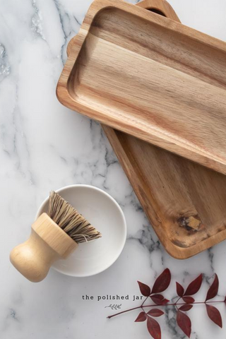 Two Wooden Trays and Dish Soap Brush on a Marble  Bathroom Counter